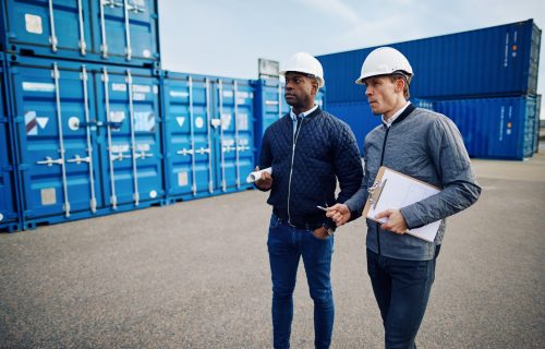 Two engineers wearing hardhats and talking together while standing in a freight yard full of shipping containers